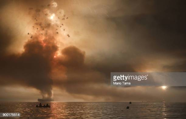 Revelers watch from a boat as fireworks are launched from barges over Copacabana beach on January 1 2018 in Rio de Janeiro Brazil Fireworks were...