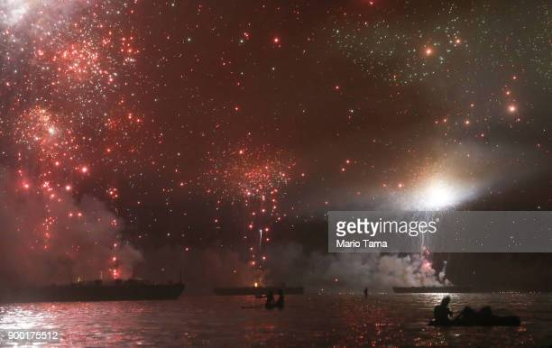 Revelers watch from boats as fireworks are launched from barges over Copacabana beach on January 1 2018 in Rio de Janeiro Brazil Fireworks were...
