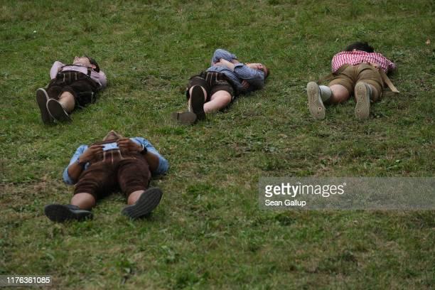 Revelers wearing lederhosen sleep on a hillside near beer tents on the second day of the 2019 Oktoberfest on September 22 2019 in Munich Germany This...