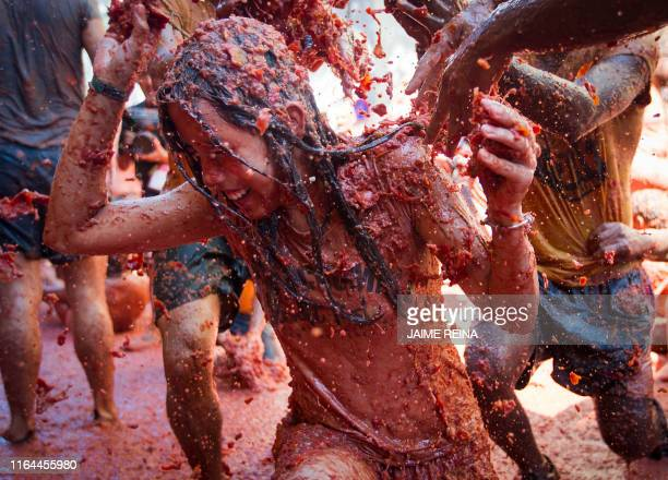 A reveller covered in tomato pulp takes part in the annual Tomatina festival in the eastern town of Bunol on August 28 2019 The iconic fiesta which...