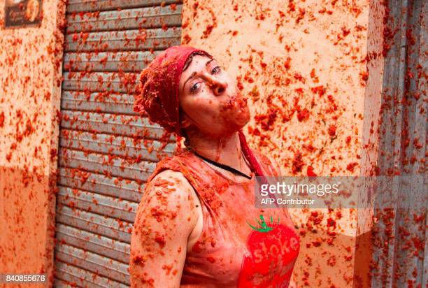 A reveller covered in tomato pulp takes part in the annual 'Tomatina' festival in the eastern town of Bunol on August 30 2017 The iconic fiesta which...