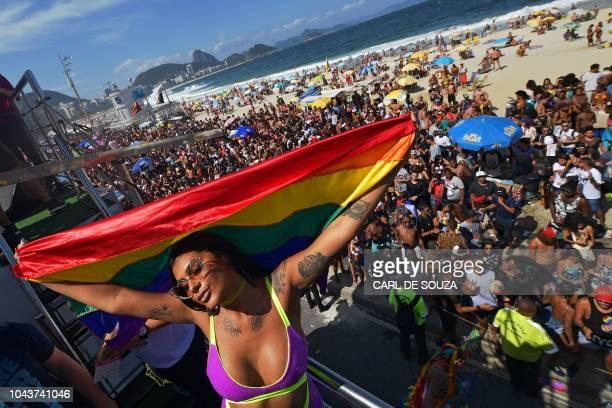 A reveller displays a rainbow flag during the Gay Pride parade in Rio de Janeiro Brazil on September 30 2018