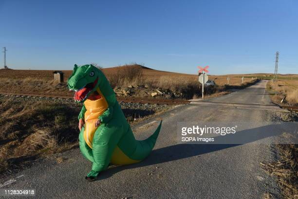 A reveller dressed as a dinosaur is seen walking along a road during the Carnival The small village of Villalba celebrates the first day of carnival...