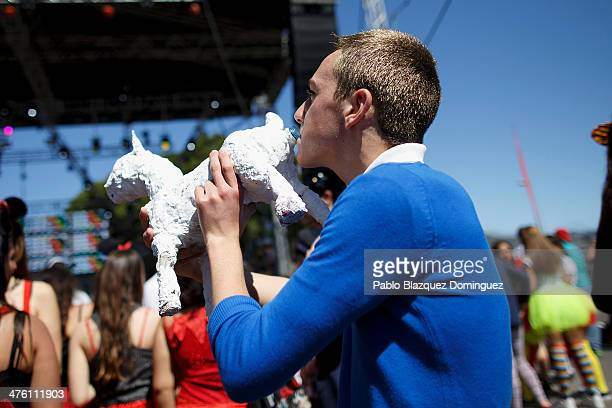 A reveller dressed as Tintin drinks from a bottle depicting Tintin's dog 'Milou' during the Santa Cruz de Tenerife Carnival on March 2 2014 in Santa...