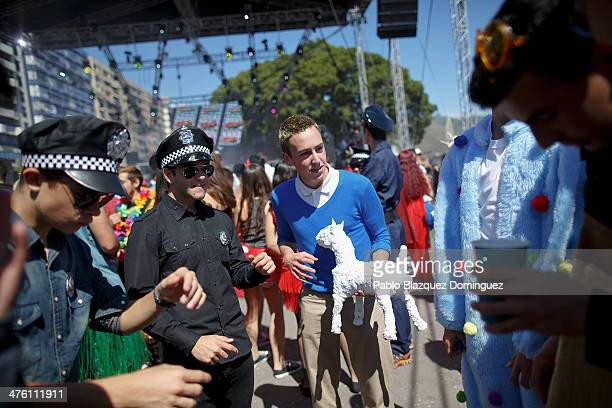 A reveller dressed as Tintin holds a bottle depicting Tintin's dog 'Milou' as he dance with revellers during the Santa Cruz de Tenerife Carnival on...