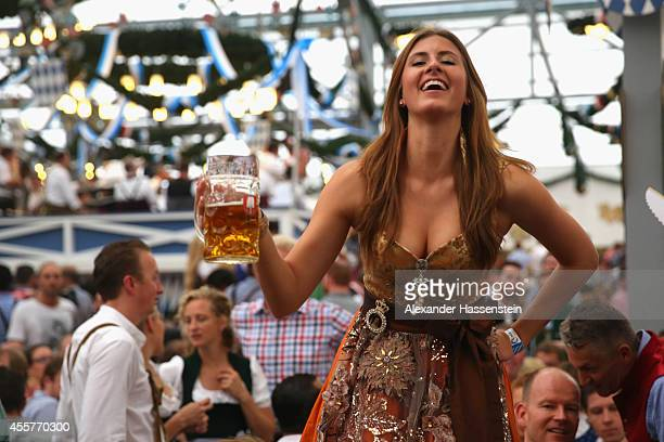 A reveller dressed in traditional Bavarian clothing `Dirndl` holds a beer mug at Schottenhamel beer tent at the opening day of the 2014 Oktoberfest...