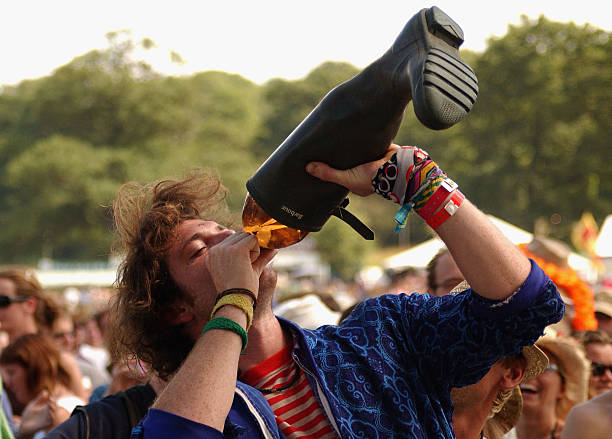 A reveller drinks cider from a wellington boot during the third day of the Big Chill music festival at Eastnor Castle Deer Park in the Malvern Hills...