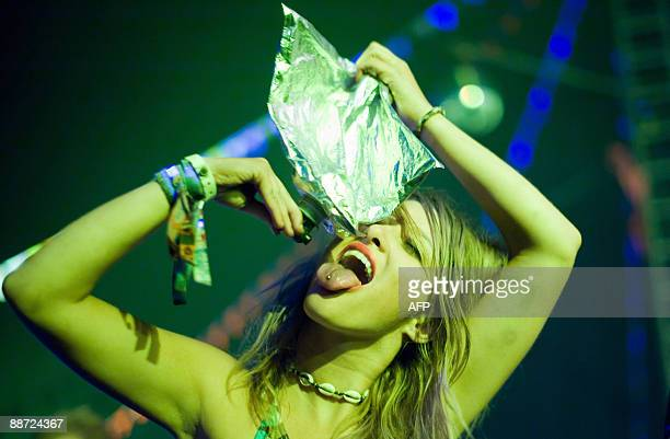 A reveller drinks from a wine pouch as French DJ Missill performs in one of the dance tents in the early hours of the third day of the annual...