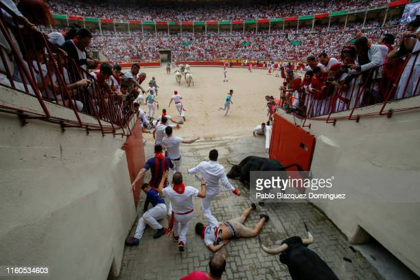 A reveller falls while running with the Puerto de San Lorenzo's fighting bulls as they enter the bullring during the second day of the San Fermin...
