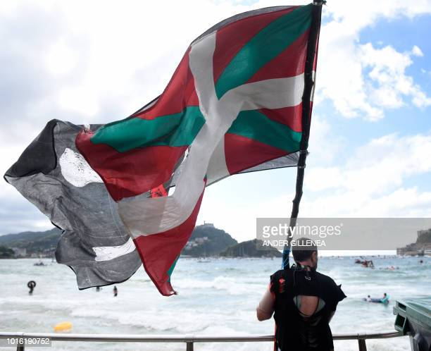 A reveller holds a Basque and a pirate flags during the celebration of the Abordaia Festival during the festivities of the Spanish Basque city of San...
