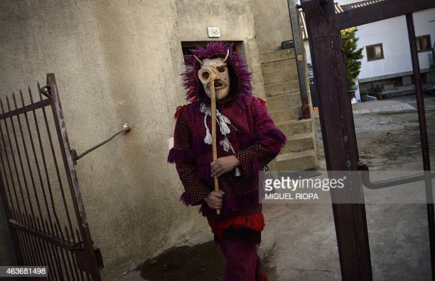 A reveller in carnival garb and wooden mask carries a stick during the traditional Celtic carnival 'Caretos' in the Portuguese village of Vila Boa de...