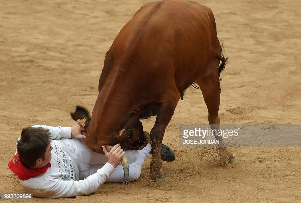 TOPSHOT A reveller is tossed by a heifer bull during festivities in the bullring on the first day of the San Fermin bull run festival in Pamplona...