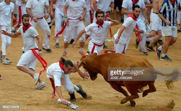 A reveller is tossed by a heifer bull during festivities in the bullring on the first day of the San Fermin bull run festival in Pamplona northern...