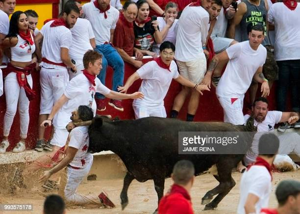 A reveller is tossed by a heifer bull during festivities in the bullring on the second bull run of the San Fermin festival in Pamplona northern Spain...