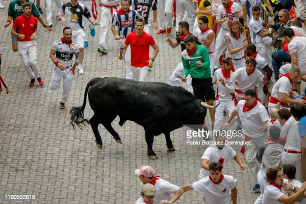 A reveller is tossed by a Puerto de San Lorenzo's fighting bull before entering the bullring during the second day of the San Fermin Running of the...