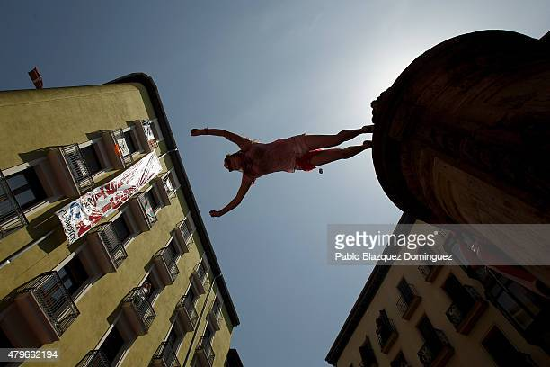A reveller jumps from a fountain to be caught by the crowd at Plaza de Navarreria during the opening day or 'Chupinazo' of the San Fermin Running of...
