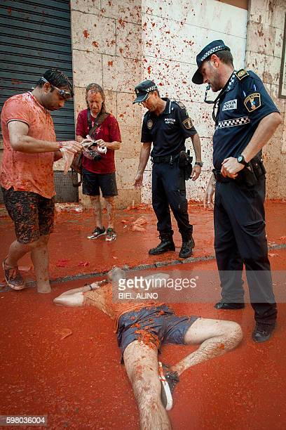 A reveller lies in tomato pulp as police stand above during the annual 'tomatina' festivities in the village of Bunol near Valencia on August 31 2016...