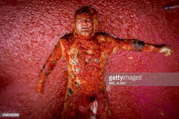 A reveller lies in tomato pulp during the annual 'tomatina' festivities in the village of Bunol near Valencia on August 31 2016 Today at the annual...