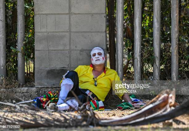 Reveller named 'Congo' rests after the Carnival parade in Barranquilla Colombia on February 11 2018 / AFP PHOTO / Luis ACOSTA
