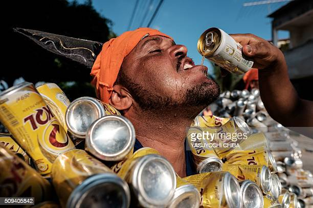 A reveller of Bloco da Latinha a street carnival group has some beer during a parade on the last day of carnival in Madre de Deus Bahia State Brazil...