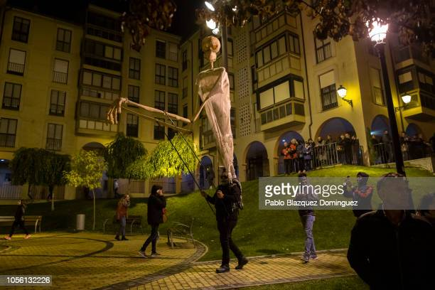 A reveller performs with a giant puppet during the 'Night of the Souls' parade on November 1 2018 in Soria Spain 'La Noche de las Animas takes place...