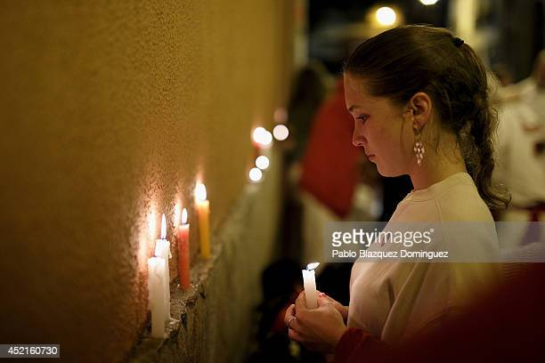 A reveller places a candle behind the Town Hall after singing the 'Pobre de Mi' song that marks the end of the San Fermin festival on July 15 2014 in...