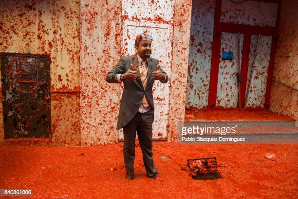A reveller pose for photographers as he enjoys the atmosphere in tomato pulp while participating the annual Tomatina festival on August 30 2017 in...