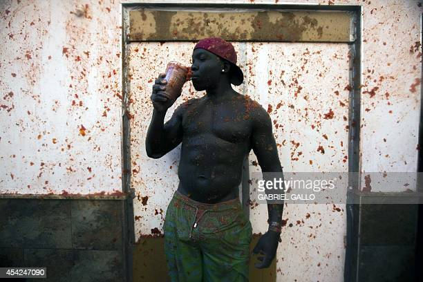A reveller poses during the annual 'tomatina' festivities in the village of Bunol near Valencia on August 27 2014 Some 22000 revellers hurled 130...