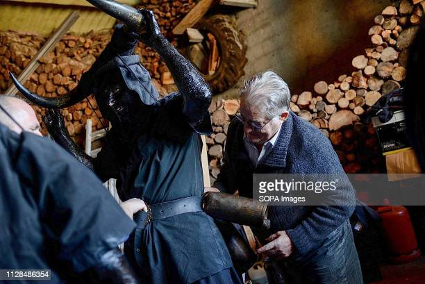 A reveller seen being dressed in oil bull horns and cowbells to represent the devil during a traditional carnival celebration in the small village of...