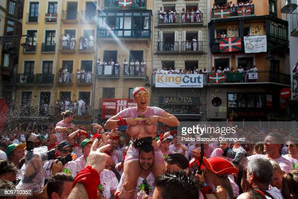 A reveller shows her breast as she enjoys the atmosphere during the opening day or 'Chupinazo' of the San Fermin Running of the Bulls fiesta on July...