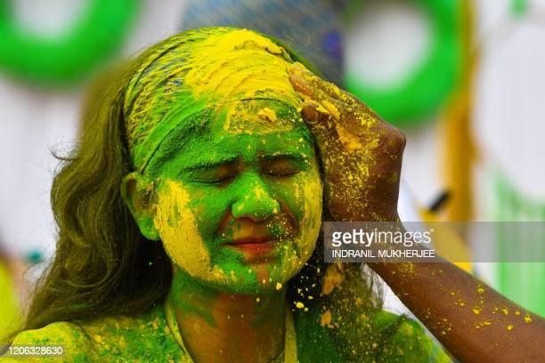 A reveller smeared in colour powder celebrates the Holi the spring festival of colours in Mumbai on March 10 2020