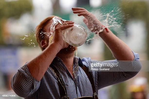 A reveller spills beer as he tries to empty his stein in one sitting at the Hofbraeu tent on the opening day of the 2015 Oktoberfest on September 19...