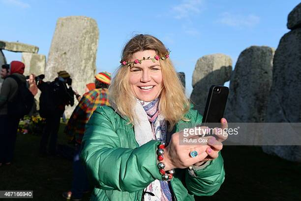 A reveller takes a selfie during celebrations marking the spring equinox at Stonehenge on March 21 2015 in Wiltshire England An estimated 700 pagans...