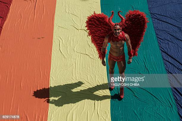TOPSHOT A reveller takes part in the 21st Rio LGBT pride parade at Copacabana beach in Rio de Janeiro Brazil on December 11 2016 / AFP / YASUYOSHI...