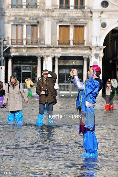 A reveller takes pictures on a flooded Piazza San Marco during Venice carnival on February 12 2010 The acqua alta is a convergence of high tides and...