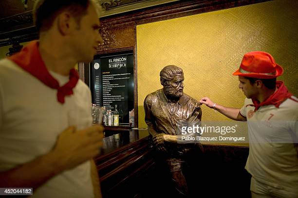A reveller touches a statue depicting Ernest Hermingway in 'El Rincon de Hermingway' bar during the sixth day of the San Fermin Running Of The Bulls...