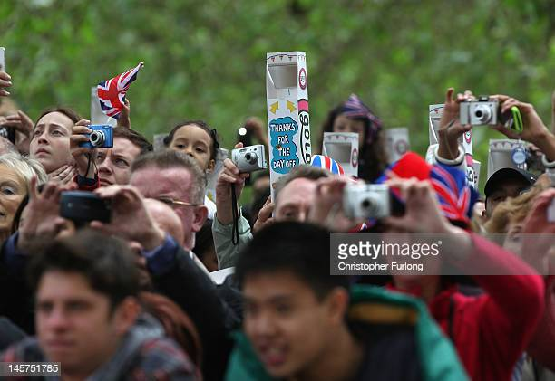 A reveller uses a periscope hoping to get a glimpse of the Queen during the carriage procession on June 5 2012 in London England For only the second...