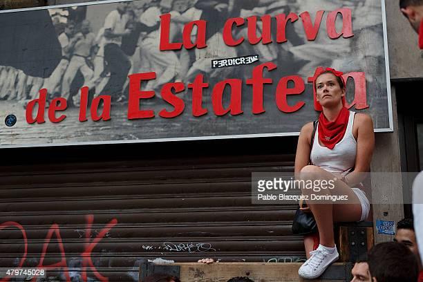 A reveller waits for the start of the running of the bulls at the 'Curva de la Estafeta' during the second day of the San Fermin Running Of The Bulls...