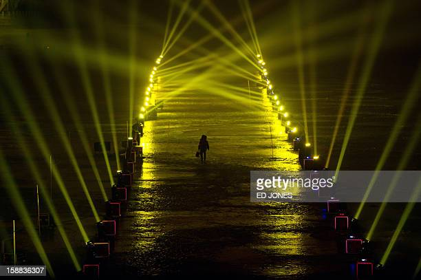 A reveller walks on a frozen lake between spotlights during a countdown event for the new year at the Summer Palace in Beijing on December 31 2012...