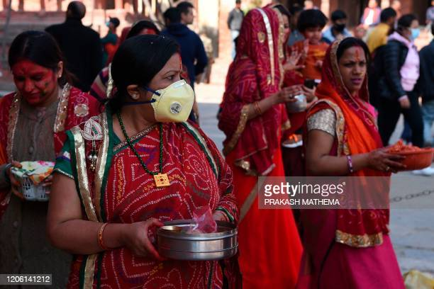 Reveller wearing a facemask amid fears of the spread of COVID-19 novel coronavirus, arrives to celebrate Holi, the spring festival of colours, in...