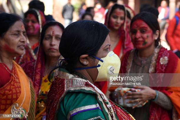 A reveller wearing a facemask amid fears of the spread of COVID19 novel coronavirus arrives to celebrate Holi the spring festival of colours in...
