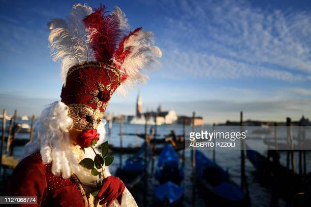 TOPSHOT A reveller wearing a mask and a period costume smells a rose as he takes part in the Venice Carnival on February 24 2019 in Venice