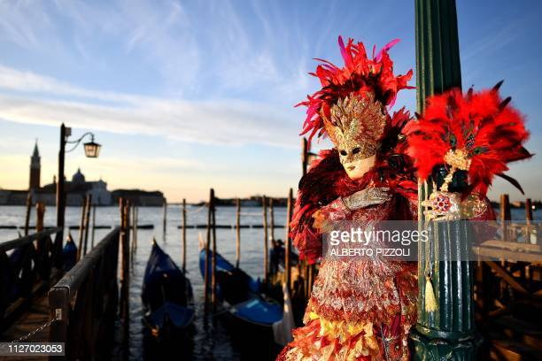 Reveller wearing a mask and a period costume takes part in the Venice Carnival on February 24, 2019 in Venice.