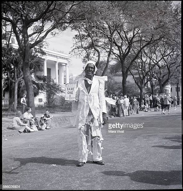 A reveller wears a ragged white costume to march in a parade for Mardi Gras New Orleans Louisiana circa 1950