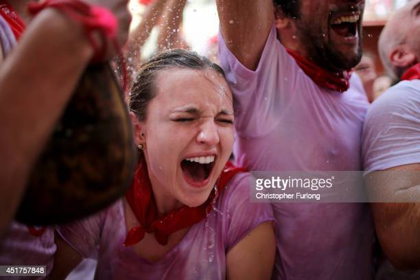 Revellers are soaked in water and wine thrown from balconies during the opening day or 'Chupinazo' of the San Fermin Running of the Bulls fiesta on...