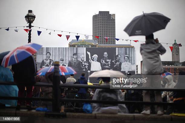 Revellers arrive early braving the rain to secure their position near Blackfriars Bridge to view the Thames Diamond Jubilee River Pageant on June 3...
