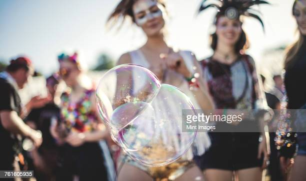 Revellers at a summer music festival large soap bubbles in foreground.