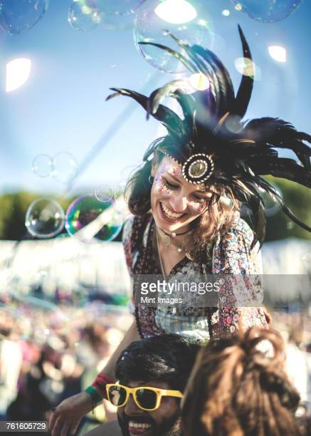 revellers at a summer music festival young man wearing yellow sunglasses carrying woman wearing feather headdress on his shoulders. - feather fan stock-fotos und bilder