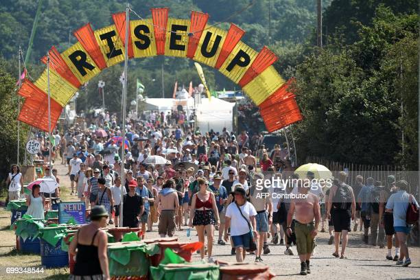 Revellers attend the Glastonbury Festival of Music and Performing Arts on Worthy Farm near the village of Pilton in Somerset South West England on...