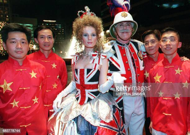Revellers attending a handover party dressed in clothing dipicting British and Chinese national colours pose for a photograph 01 July outside of the...